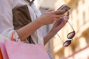 Woman checking her smartphone while shopping